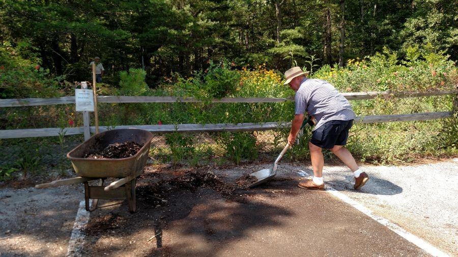 Man shoveling up debris into a wheelbarrow